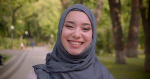 hijab的与明亮做愉快放光成照相机走在公园的回教妇女画象  股票视频