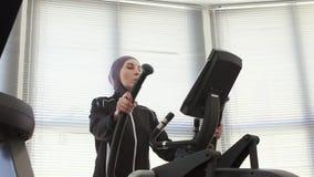 hijab的俏丽的女孩在体育健身机器 股票视频
