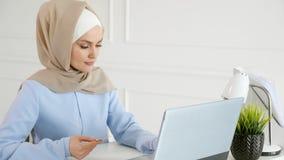 hijab的回教妇女在网上买与信用卡和膝上型计算机 影视素材
