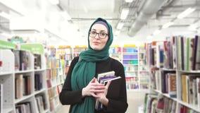 hijab的女孩与书在手上在图书馆里 股票视频