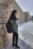 hijab的女孩听到从智能手机的音乐通过耳机 库存照片