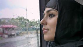 hijab的年轻回教妇女在多雨窗口里在公共汽车,运输概念,都市概念,天气概念上观看 股票视频