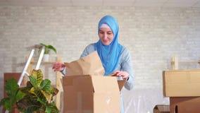hijab的年轻回教妇女在移动以后拆卸一个箱子盘 股票录像