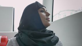 hijab的年轻回教妇女在窗口里在公共汽车,多雨天气,运输概念,都市概念上观看 股票录像
