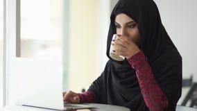 hijab的年轻回教妇女坐在咖啡馆喝一杯咖啡和使用她的膝上型计算机的 她搜寻为 股票视频