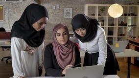 hijab的年轻回教妇女的谈论项目和指向在膝上型计算机的,谈论经营计划在现代办公室 影视素材