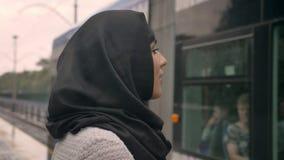 hijab的年轻回教妇女观看火车怎么受到下雨,宗教概念,运输概念,天气 股票视频