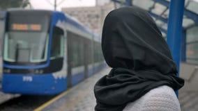 hijab的年轻回教妇女观看火车怎么来临,下雨,宗教概念,都市概念 股票视频