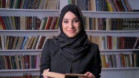 hijab的年轻美丽的回教女孩是阅读书,观看在照相机,微笑,在背景的书架,宗教 影视素材