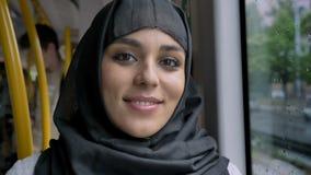 hijab的年轻美丽的回教妇女在公共汽车,运输概念,都市概念,天气概念上观看在照相机 股票视频