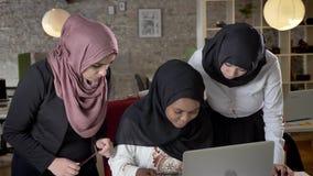 hijab的年轻黑人回教妇女谈话与关于项目的同事在膝上型计算机在现代办公室 股票视频