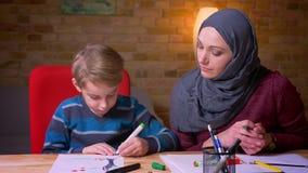 hijab的快乐的回教母亲和她的与标志的小儿子画的图片在舒适家庭环境 影视素材
