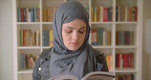 hijab的读书的年轻可爱的回教女生特写镜头画象看照相机在学院 股票录像