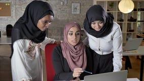 hijab的谈论事务计划和指向在膝上型计算机的年轻回教妇女的队,谈论项目在现代 股票录像