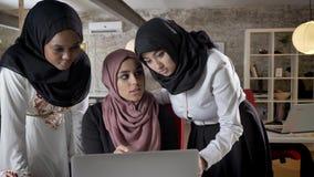 hijab的谈论项目和指向在膝上型计算机的年轻回教妇女的企业队,谈论事务计划  影视素材