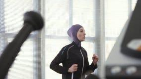 hijab的运动员女孩在一台连续模拟器缓慢的mo 股票录像