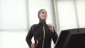 hijab的运动员女孩在一台连续模拟器 股票录像