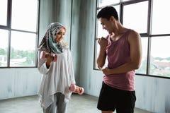 Hijab женщины делая тренировки веса с тренером помощи личным стоковые фото