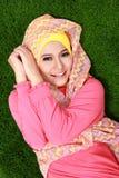 Hijab молодой мусульманской девушки нося лежа на траве и смотря ca стоковое изображение rf