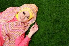 Hijab молодой мусульманской девушки нося лежа на траве с космосом экземпляра стоковая фотография rf