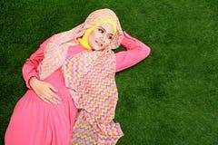 Hijab молодой мусульманской девушки нося лежа на траве стоковое фото