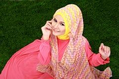 Hijab молодой мусульманской девушки нося сидя на траве и смотря стоковая фотография