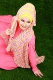 Hijab молодой мусульманской девушки нося сидя на траве Стоковые Изображения