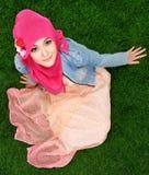 Hijab мусульманской девушки нося сидя на траве Стоковые Фотографии RF