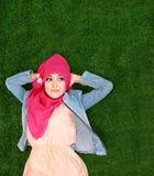 Hijab d'uso della ragazza che si trova sull'erba che rispetta copyspace Fotografia Stock