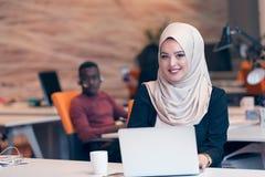 Hijab de port arabe de femme d'affaires, fonctionnant dans le bureau de démarrage images stock