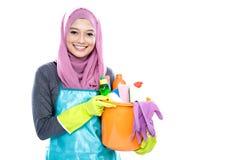 Hijab de port de femme au foyer jugeant le seau plein des alimentations stabilisées photo stock
