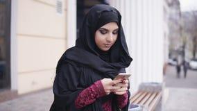 Hijab que lleva de la mujer atractiva joven que se coloca en la calle, mecanografiando un mensaje en su teléfono móvil Tiro a cám metrajes