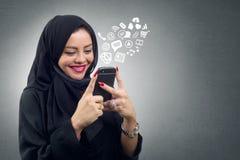 Hijab que lleva de la señora árabe usando su móvil con los iconos virtuales de los apps Fotografía de archivo libre de regalías