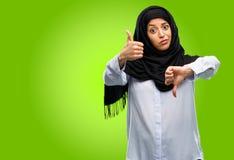 Hijab vestindo da mulher árabe nova isolado sobre o fundo verde fotos de stock