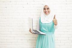 hijab vestindo da mulher asiática que guarda o portátil e que dá os polegares acima fotos de stock royalty free