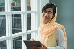 Hijab vestindo da mulher mu?ulmana usando o PC da tabuleta imagens de stock