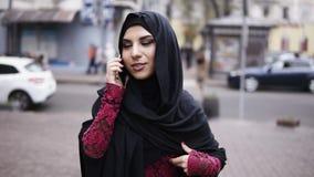 Hijab vestindo de sorriso da mulher atrativa dos jovens que anda na rua na cidade que fala em seu telefone celular Tiro Slowmotio video estoque