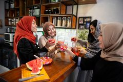 Hijab women enjoy sweet drink when breaking fast together. At home royalty free stock photo