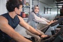 Hijab y amigo musulmanes de la mujer en el gimnasio que hace ejercicios cardiios Imágenes de archivo libres de regalías