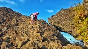 Hijabmeisje die op piek van rotsberg beklimmen royalty-vrije stock foto
