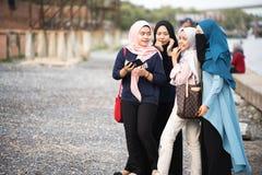 Hijabs M?dchen, das auf der K?ste sich entspannt stockfoto