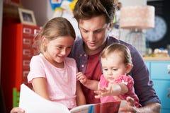 Hijas de Reading Book With del padre en dormitorio Imagen de archivo libre de regalías