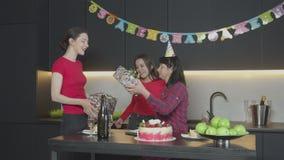 Hijas que dan los regalos de cumpleaños a la madre feliz almacen de metraje de vídeo