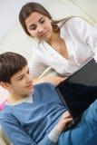 Hijo adolescente con la madre joven con el ordenador portátil Fotos de archivo libres de regalías