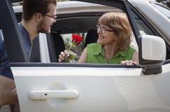 Hijo adolescente que da a su mamá una rosa roja en el coche Imagen de archivo libre de regalías