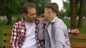 Hijo adolescente que habla con el padre en banco, secretos susurrantes y sonriendo, confianza almacen de metraje de vídeo