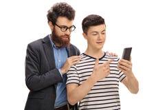 Hijo adolescente que muestra algo en un teléfono a su padre Foto de archivo libre de regalías