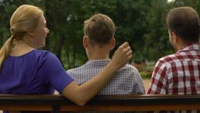 Hijo adolescente que se sienta con los padres en banco y que habla de las vacaciones, confianza almacen de video