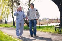 Hijo adulto que camina con su padre mayor Foto de archivo libre de regalías