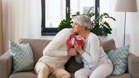 Hijo adulto que da las flores a la madre mayor en casa almacen de metraje de vídeo